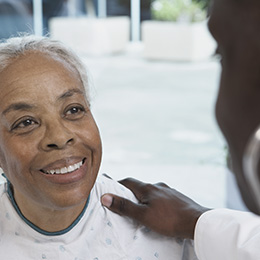 doctor speaking with smiling older woman