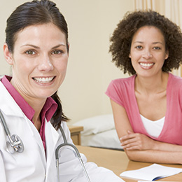 female doctor sitting at desk with woman smiling